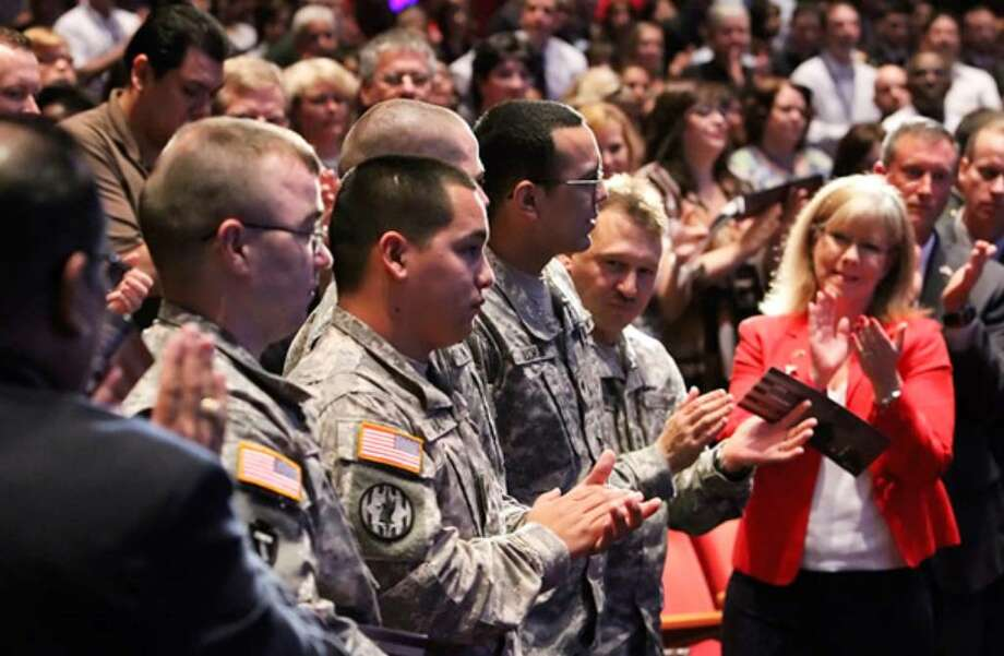 Soldiers in the Warrior Transition Battalion at Fort Sam Houston are applauded for their service during the Memorial Day program at USAA, witnessed by about 2,000 people at the company's headquarters and thousands more at regional sites.