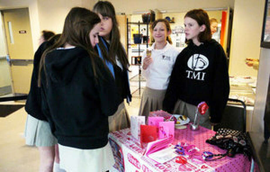 TMI student Mary Gibbons (right) helps other students at the JuniorAct club fundraiser for Haiti.