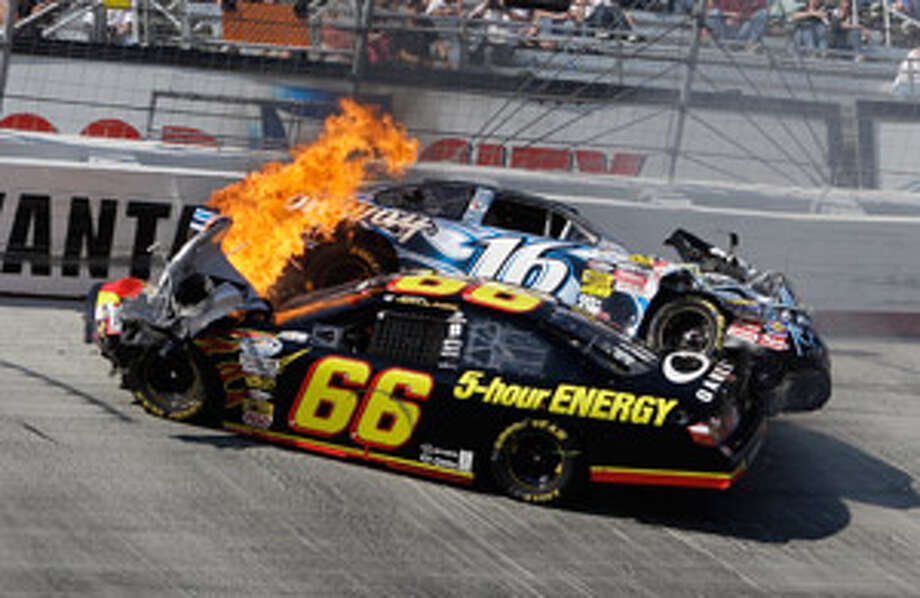 Fire erupts from Steve Wallace's car (66) as Colin Braun's car rests on top after crashing during the Nationwide Series Scotts Turf Builder 300 on Saturday at Bristol, Tenn.