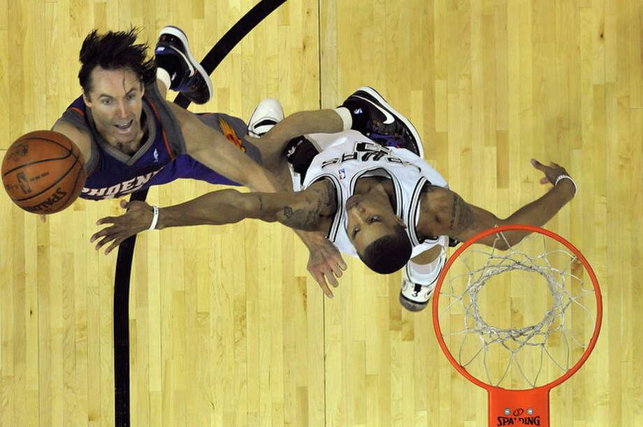 Spurs' George Hill defends against the Phoenix Suns' Steve Nash. / San Antonio Express-News