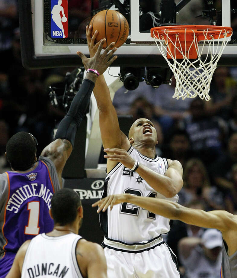 Spurs' Richard Jefferson (center) goes up for shot against the Phoenix Suns' Amar'e Stoudemire (left). / San Antonio Express-News
