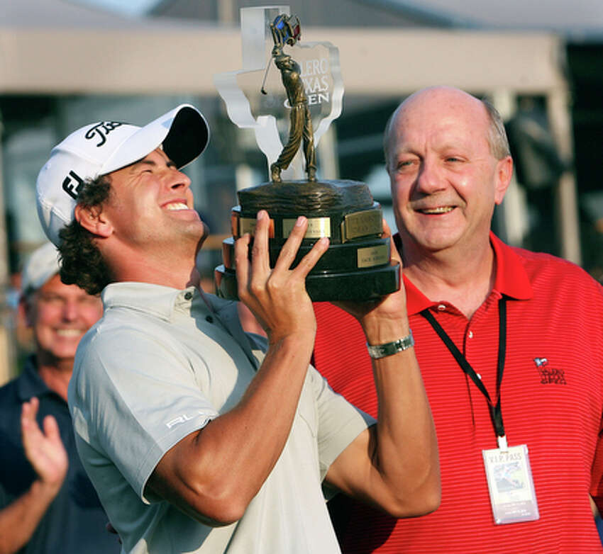 Adam Scott hoists the Valero Texas Open trophy as Valero's Mike Ciskowski looks on during the award ceremony following play at the AT&T Oaks Course at TPC San Antonio on May 15, 2010. Scott shot a final round 67 to finish at 14 under par for the win.