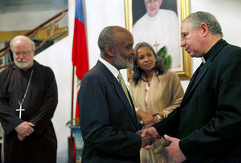 San Antonio Archbishop Jos? Gomez expresses his condolences and solidarity with the Haitian people to Haitian President Rene Preval and his wife, first lady Elisabeth Preval, while Cardinal Sean O'Malley, Boston's archbishop, stands by Monday in Petionville, Haiti.