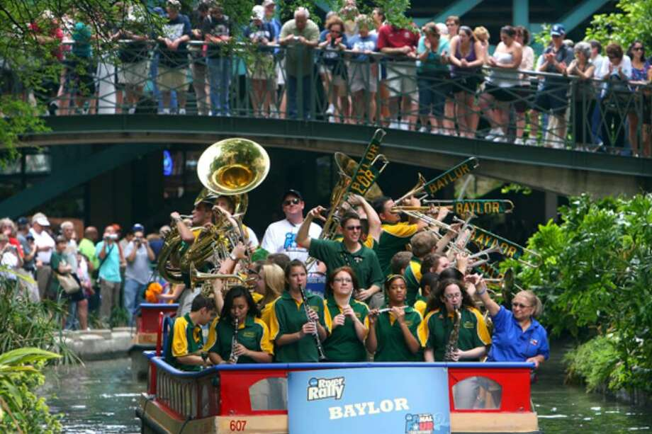 The Baylor band enters the Rivercenter Mall lagoon during the NCAA River Rally on Sunday.