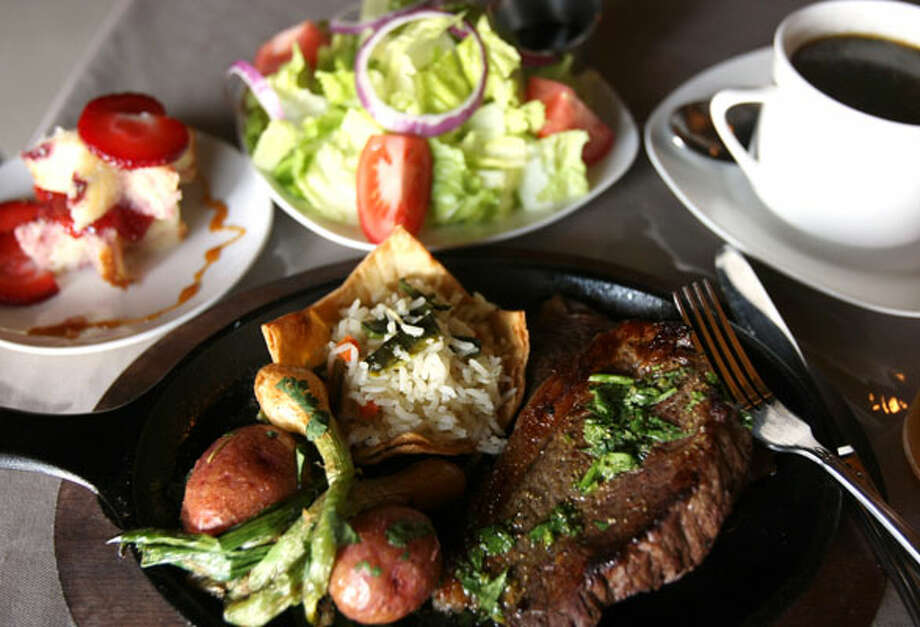 One of Charola's daily specials features a garden salad (clockwise from top), three-bean soup, sirloin steak in a chimichurri sauce, red potatoes, onions and rice and dessert.
