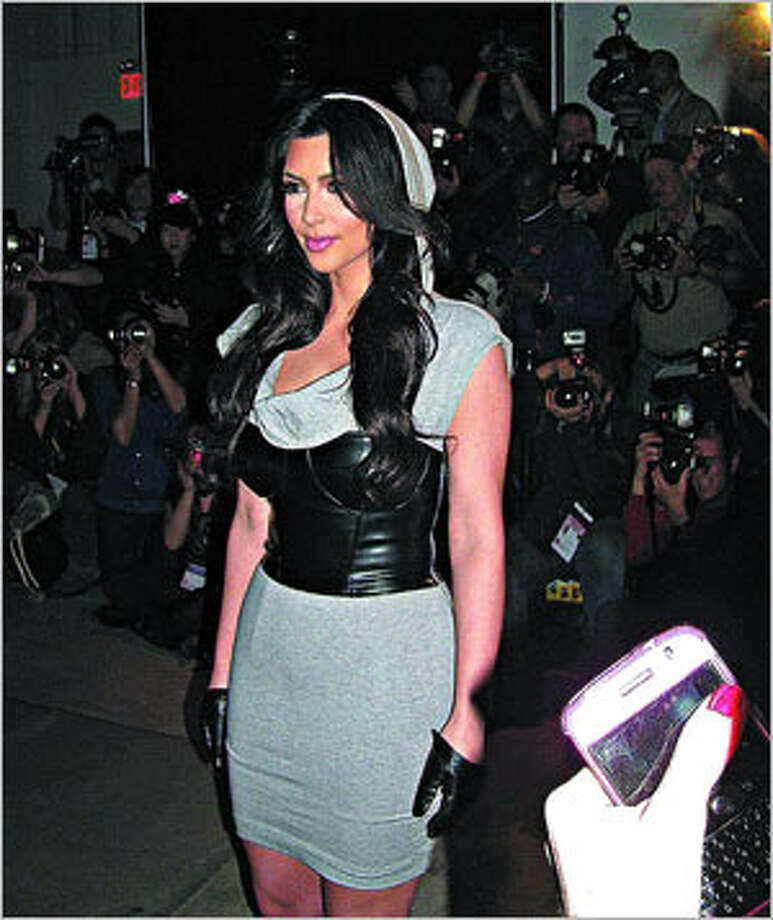 Here Kim wears her own design (a jersey hooded dress teamed with a leather corset) at her beb-Kardashians shows during New York fashion Week earlier this year.