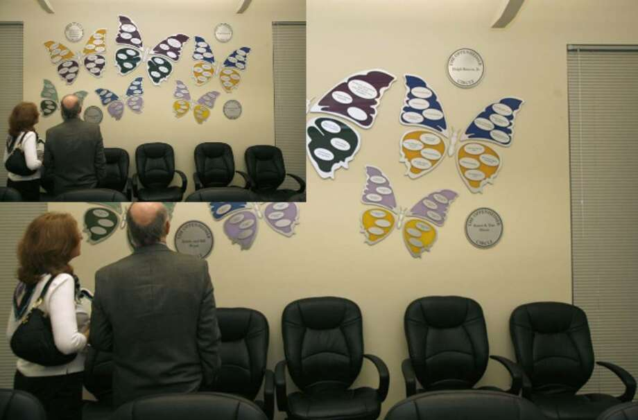 Harriet and David Oppenheimer look over butterfly wall art that acknowledges major donors to the Oppenheimer Center.