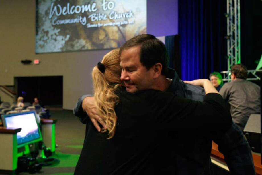 Pastor Robert Emmitt hugs congregant Judy Manzano after a service. Every month, Community Bible Church attracts at least 150 new members, a common estimate for the average-sized U.S. church. Twenty years ago, 110 people came to the church's first service at a hotel.