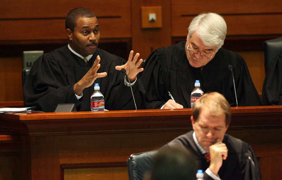 Justice Dale Wainwright (left) gestures during a hearing at St. Mary?s University School of Law as justices Nathan L. Hecht (right) and Don R. Willett (front) listen.
