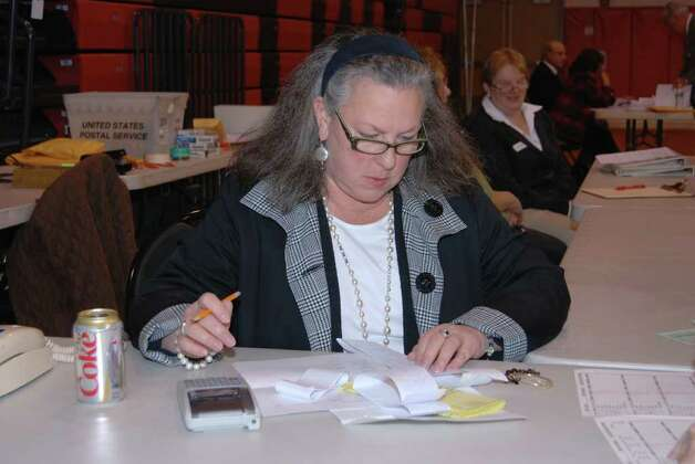 Town Clerk Claudia Weber tallies the long list of counted votes Photo: Jeanna Petersen Shepard / New Canaan News