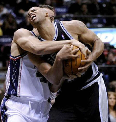 The Nets' Kris Humphries (left) ties up the Spurs' Richard Jefferson while on his way to the basket during New Jersey's 10th victory.