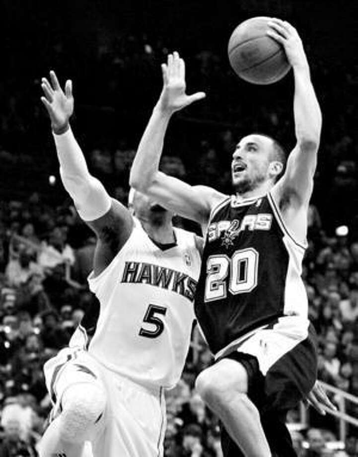 Spurs guard Manu Ginobili puts up a shot in front of Atlanta's Josh Smith during the first half Sunday night.