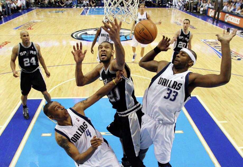Spurs' Tim Duncan grabs for a rebound between Mavericks' Caron Butler and Brendan Haywood in Game 2 of the first round of the Western Conference playoffs Wednesday April 21, 2010 at the American Airlines Center in Dallas, Tx. The Spurs won 102-88. / © 2010 SAN ANTONIO EXPRESS-NEWS