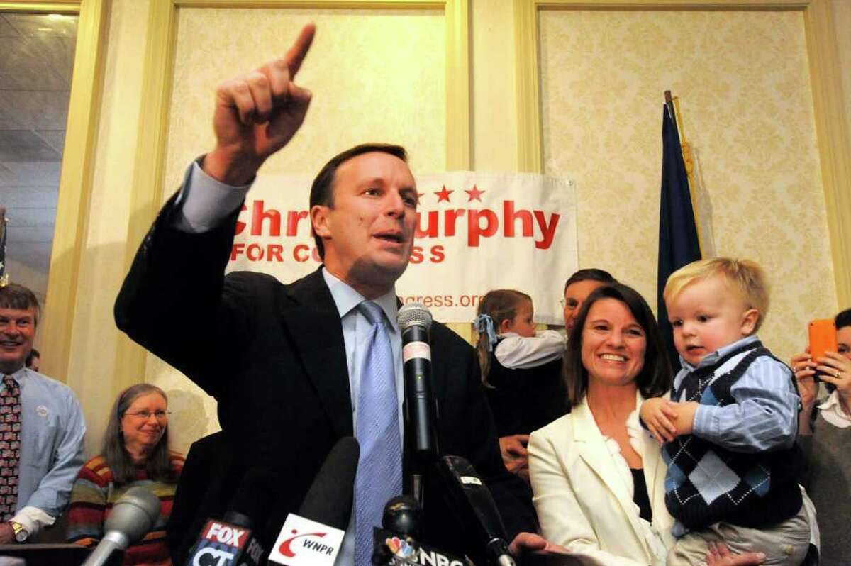 U.S. Rep.Chris Murphy announces victory standing with his son, Owen, and his wife Cathy Holahan, from his headquarters in Waterbury, Tuesday, Nov.2, 2010.