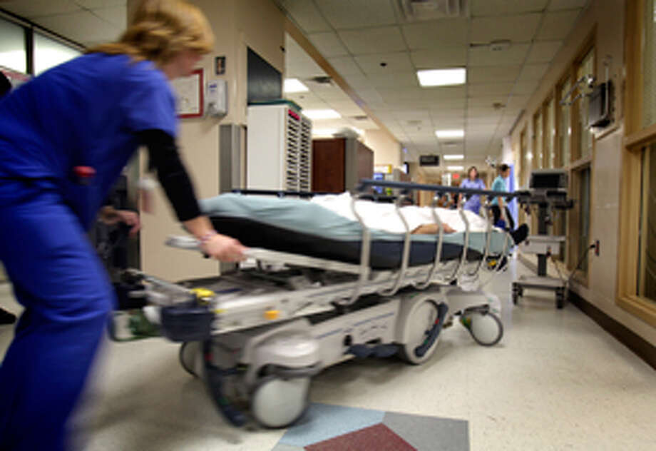 A University Hospital nurse wheels a patient to a new position in the emergency room.