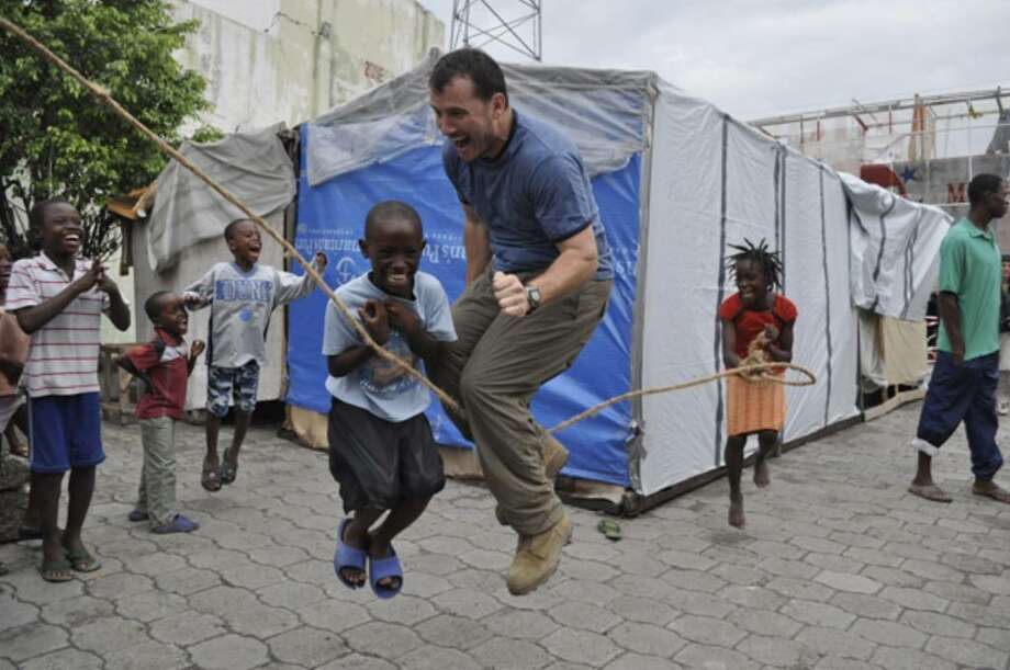 "Justin Yarborough, one of the founders of the non-profit ""We Hear Your Voice,"" joins an impromptu jump-rope competition with children in a Port-au-Prince neighborhood."