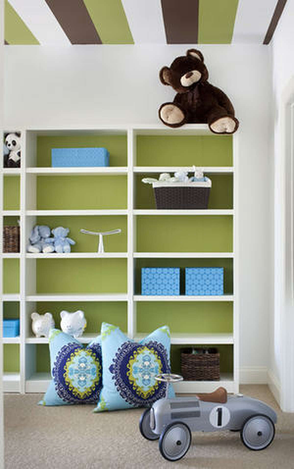 In this playroom featured on Decor Demon, designer Brian Patrick Flynn adds color to the ceiling and back of the bookcases.