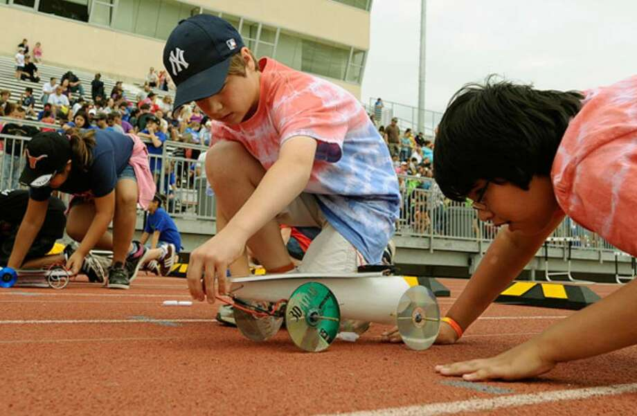Thornton Elementary School students Morgan Yost (left) and Brian Skilling prepare their entry for the Texas Solar Car Races at Gustafson Northside Stadium.