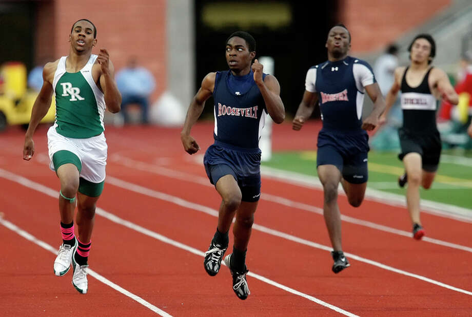 Roosevelt's Bruce Crum (center) looks back at Reagan's Jurell Henry as they sprint toward the finish line in the 400 Meter Dash at the 26-5A Track Meet at Heroes Stadium on Friday, April 16, 2010. Crum took first. Top three finishers move onto the state meet. / San Antonio Express-News