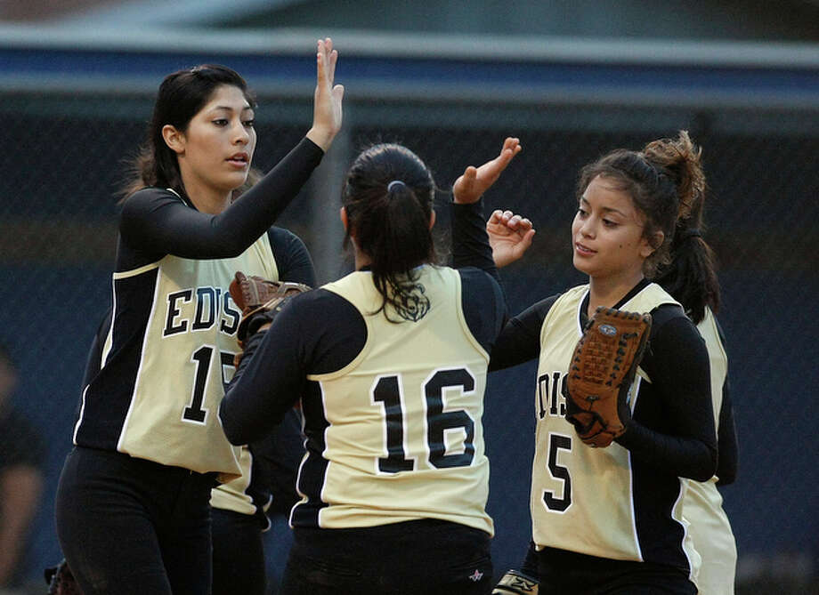 Edison's Regina Morales gives high-fives to teammates during their game against Burbank on Tuesday, April 13, 2010. Edison defeated Burbank, 2-1. / San Antonio Express-News