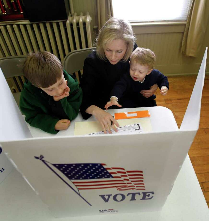 U.S. Sen. Kirsten Gillibrand, D-N.Y., votes beside her sons Theo, left, and Henry, at the Becraft Pumper Company in Greenport, N.Y., Tuesday, Nov. 2, 2010. (AP Photo/Mike Groll) Photo: Mike Groll