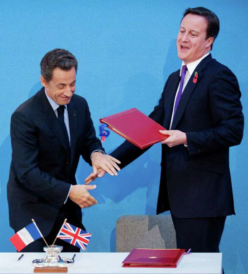 French President Nicolas Sarkozy, left, and Britain's Prime Minister David Cameron joke after signing a treaty at an Anglo-French summit at Lancaster House in London, Tuesday Nov. 2, 2010.  Britain and France vowed to work hand-in-glove as their leaders ushered in an unprecedented era of defence cooperation by agreeing to create a joint force and share nuclear test facilities.(AP Photo/Leon Neal, pool) Photo: LEON NEAL / POOL, AFP