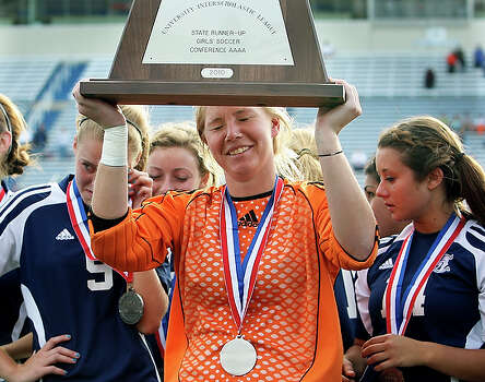 Goaltender Morgan Glick, flanked by Conner Cuevas, left, and Karis Watts, right, raises the runner-up trophy at Birkelbach Field. If you ask members of the Boerne Champions girls soccer team, they would tell you they never thought they would have made it this far. Even when their coach dangled a state tournament-or-bust carrot in front of them last fall, players laughed it off as nothing more than a motivational ploy. That didn't make Champion's 3-0 loss to Richardson Pearce any easier to accept. / © 2010 San Antonio Express-News