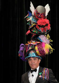 Express-News fashion editor Michael Quintanilla wears the world's tallest Fiesta hat at the Fiesta Luncheon, Style Show & Hat Contest put on by the Women's Club of San Antonio. / SAN ANTONIO EXPRESS-NEWS