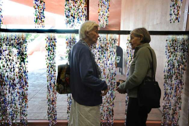 "Fredrika May (left) and Shirley Watson comment on ""Days,"" a meditative art installation commemorating the life of late philanthropist Linda Pace, in the Central Library lobby. Artist Jesse Amado spent a month installing the Linda Pace Foundation-commissioned work."