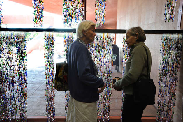 Fredrika May (left) and Shirley Watson comment on ?Days,? a meditative art installation commemorating the life of late philanthropist Linda Pace, in the Central Library lobby. Artist Jesse Amado spent a month installing the Linda Pace Foundation-commissioned work.