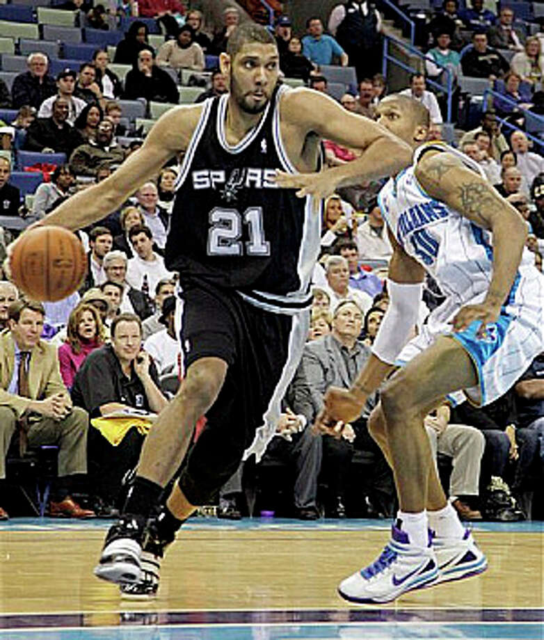 The Spurs? Tim Duncan (21) spins around the Hornets? David West and drives for two of his 22 points.