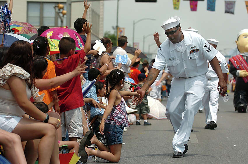 2005 Petty Officer 2nd Class Cortney Bolden, a boatswain's mate on the USS San Antonio, greets children during the Fiesta Battle of Flowers parade.