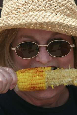 Molly Bailey of San Antonio sinks her teeth into some corn on the cob while enjoying the sights and sounds of the Taste of New Orleans at the Sunken Gardens, a favorite Fiesta event put on by the San Antonio Zulu Association. / jdavenport@express-news.net