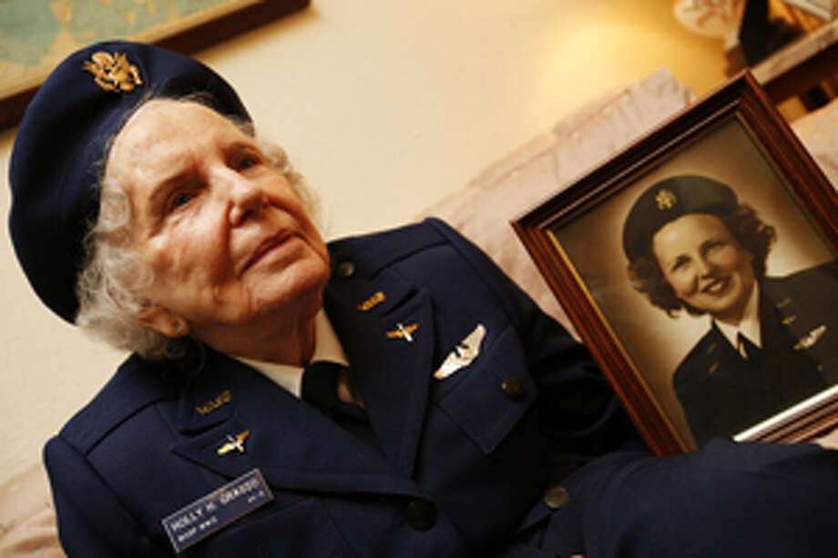 HOlly Grasso, 88, holds a portrait of herself as a member of the Women Airforce Service Pilots.