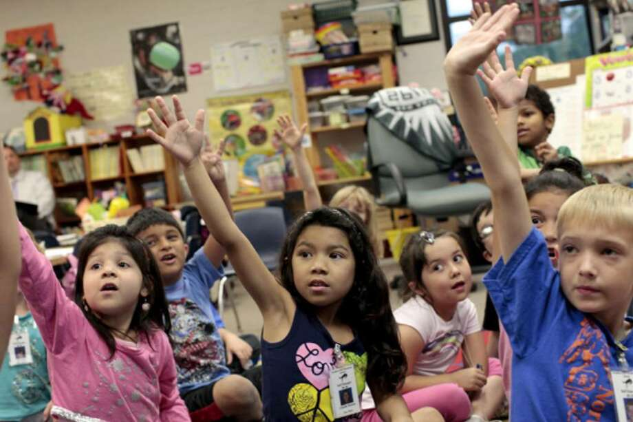 Kindergartners including Angel Meza, 5, (from left) John Contreras, 6, Giselle Barrios, 6, Madison Monita, 6, and Travis Barker, 6, raise their hands to answer a question in Cathleen Henry's kindergarten class at Northern Hills Elementary School in San Antonio on May 14, 2010.
