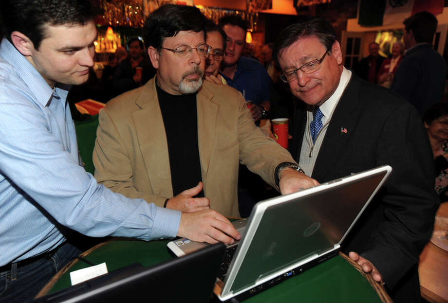 Republican primary candidate for the District 23 race Francisco Canseco, right, looks over returns with Cliff Borofsky, middle, and Scott Yeldell, left, at El Tacotote on Tuesday, March 2, 2010. / gcalzada@express-news.net