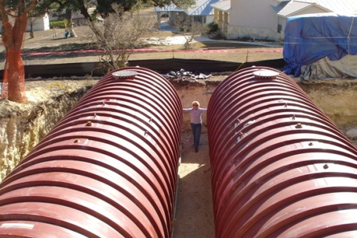 Karen Adams stands next to two 20,000-gallon rainwater collection tanks while they were being installed. Runoff from the roof results in 2,229 gallons of water for every inch of rain received.