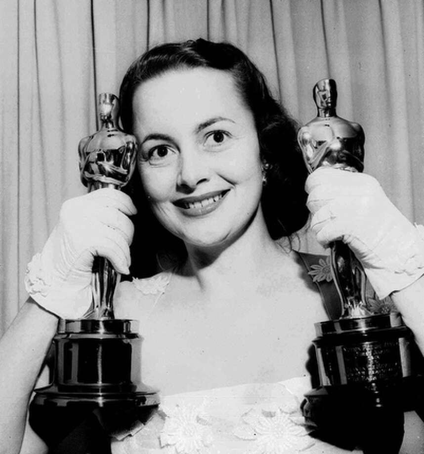 "Actress Olivia de Havilland holds her Oscar statues in this March 24, 1950, file photo. De Havilland won for her performance that year in ""The Heiress,"" and in 1946 for ""To Each His Own.""  She used to retreat to the Texas HIll Country during time off from films.  Her former home in Boerne is now the Guadalupe River Ranch, a resort center housing a spa and rustic cottages. / AP"