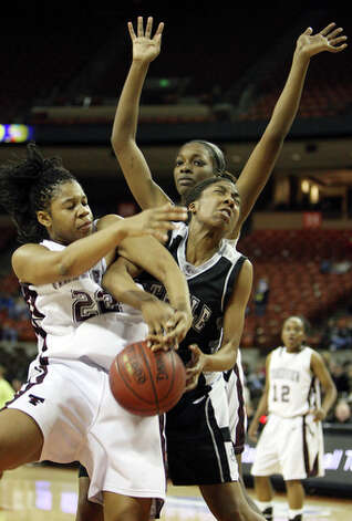 Timberview's Cree Conner and  Steele's Taylor Calvert fight for control of the ball as Timberview's Camille Redmon (rear) looks on. / eaornelas@express-news.net