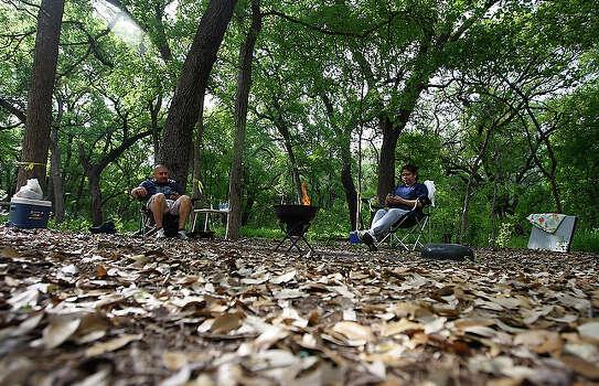 Gilbert Huchin (left) and Delfina Herrera secure their site in Brackenridge Park in 2010. / kmhui@express-news.net