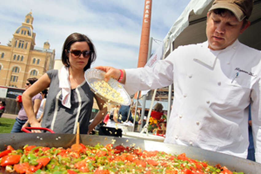 San Antonio native Emily Ford, left, watches as her husband, Ben Ford, Executive Chef of Ford's Filling Station in Los Angeles, adds chopped onions to his paella base at the 2010 Paella Challenge.