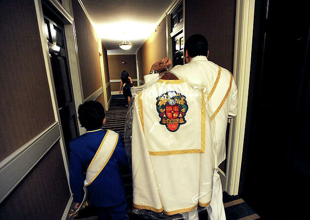 "Baltazar ""Walter"" Serna and his son, Baltazar III, leave their room in the Gunther Hotel, Friday, April 16, 2010, on their way to the elder Serna's coronation as El Rey Feo LXII. / gcalzada@express-news.net"