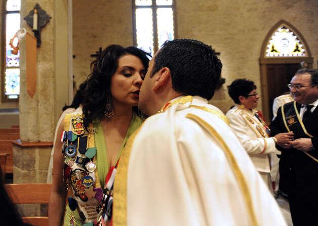 Debbie Serna kisses her husband before his coronation.