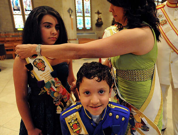 Baltazar Serna III smiles as his mother, Debbie Serna, adjusts the sash on his sister, Alejandra Serna, in San Fernando Cathedral. / gcalzada@express-news.net