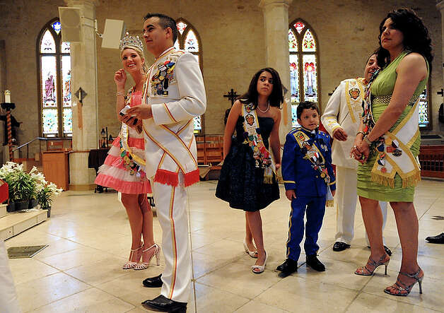 Serna, the new El Rey Feo, second from right, and his wife, Debbie, and their children Baltazar III, 8, and Alejandra 12, join others in line as they wait to leave the interior of San Fernando Cathedral for the coronation. / gcalzada@express-news.net