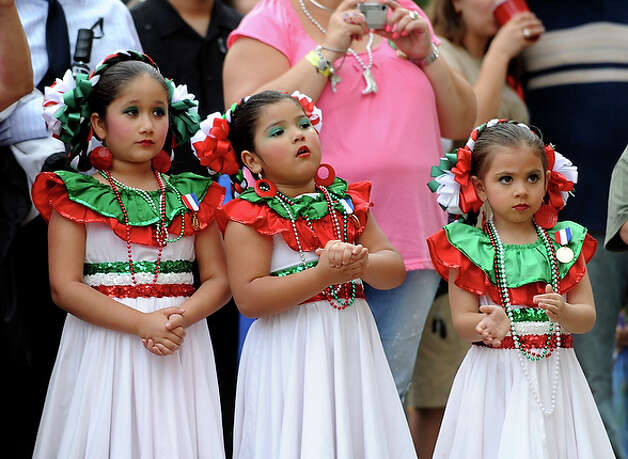 Girls in folklorico dress watch the coronation of Serna as El Rey Feo LXII in Main Plaza. / gcalzada@express-news.net