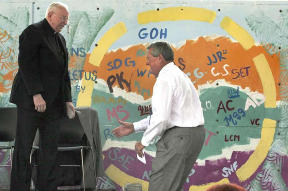 Bill Greehey (right) chairman and executive director of Haven for Hope, greets the Rev. John Leies, president emeritus of St. Mary's University, after he blessed the mural.