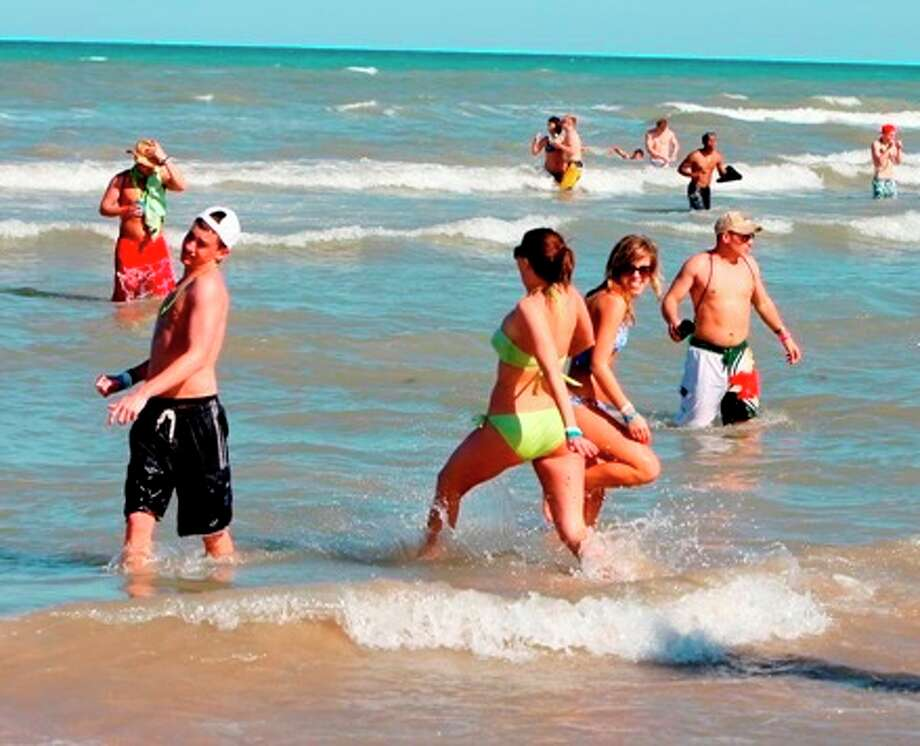 Beach goers play in the surf at South Padre Island. Texas officials are preparing for an influx of vacationers due to the oil spill along the Gulf Coast.