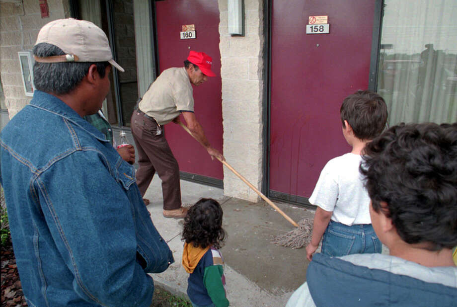 Trini, a worker at the Days Inn where Selena was shot, mops up the blood stains on April 1, 1995, at the hotel door where she was hit by the bullet that killed her.  In the foreground at left is Angel Resendez who brought his family from Port Arthur. / SAN  ANTONIO EXPRESS-NEWS