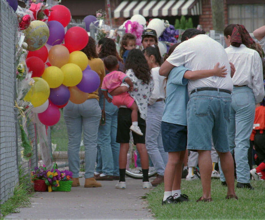 Nine year old Patricia Kingsbury hugs her mother's boyfriend Bobby Sanchez, and cries as others pass by in front of Selena's house on Blooomington St. in Corpus Christi on April 1, 1995.